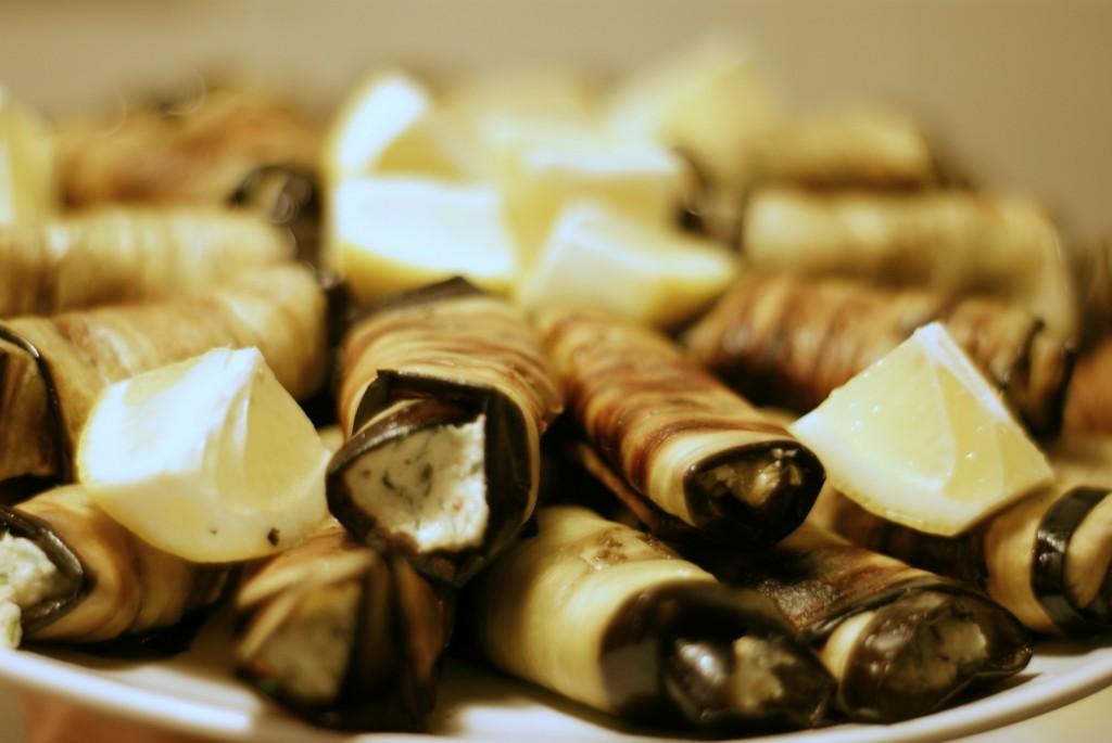 Roladki z bakłażana z miętowo-koperkowym twarożkiem podane z cząstkami cytryny.