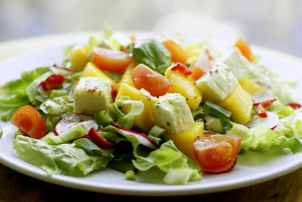 Sałata z mango, świeżymi ziołami, rzodkiewką, chili, pomidorem i białym serem okraszona miodowym winegretem.