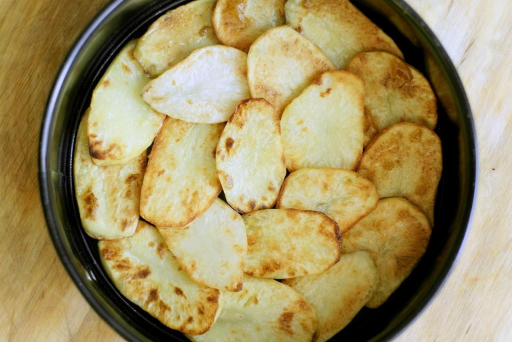 Upieczone ziemniaki ułożone w tortownicy na zakładkę.