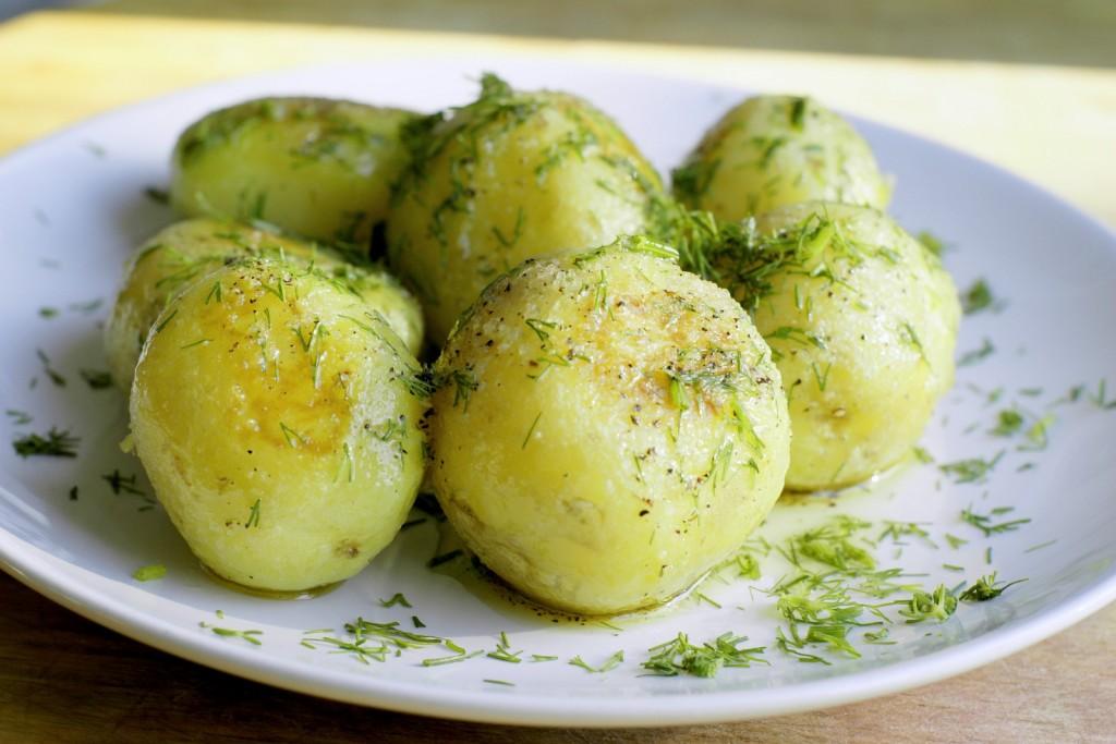 Młode ziemniaki okraszone oliwą z pieprzem i koperkiem.